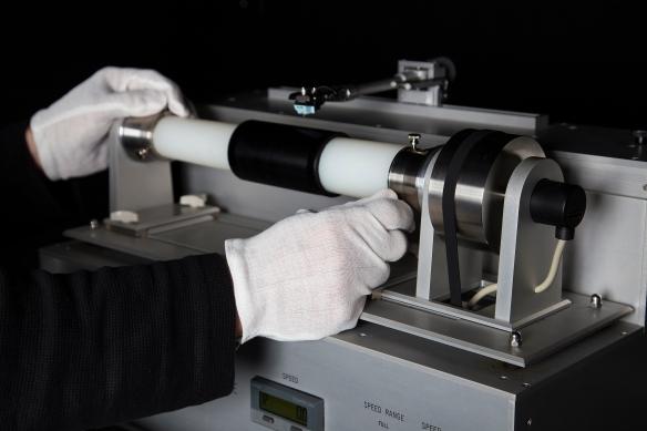 Une photographie couleur montrant un lecteur de cylindre avec un cylindre Blue Amberol passé sur un tube horizontal, ainsi qu'une aiguille oscillant au-dessus du cylindre.