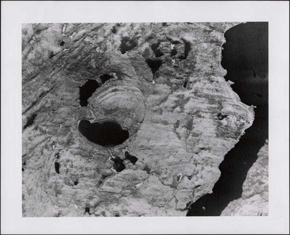 Photo aérienne d'un cratère. On peut apercevoir l'arc d'un cercle sur un terrain formé aujourd'hui de lacs et de collines.