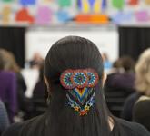 Photo couleur d'une pince à cheveux ornée de perles multicolores à l'arrière de la tête d'une femme. Celle-ci prend place dans la salle Pellan de Bibliothèque et Archives Canada, où elle écoute un groupe de conférenciers.
