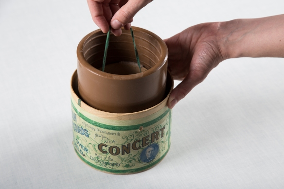 Une photographie couleur d'un cylindre de cire que l'on retire de son contenant protecteur en carton, en le soulevant à l'aide d'une corde attachée à l'intérieur du cylindre. Le mot « Concert » est imprimé sur le contenant en lettres majuscules; au-dessus, en plus petits caractères, on peut lire « National Phonograph Co, New York, U.S.A. » et en dessous, « Made at the Edison Laboratory, Orange, N.J. » [Fabriqué au laboratoire Edison, Orange, N. J.].