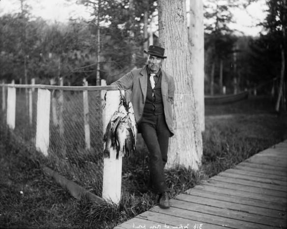Photographie en noir et blanc d'un homme portant entre autres un chapeau, un manteau et une cravate. Il est appuyé sur un poteau de clôture et tient une corde à laquelle sont attachés des poissons