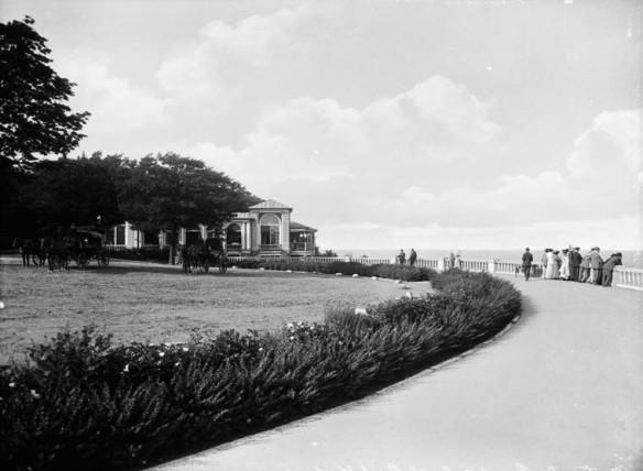 Photographie en noir et blanc d'un élégant sentier délimité par une clôture de pierres d'un côté et menant à un petit édifice. Des chevaux se reposent sous les arbres.
