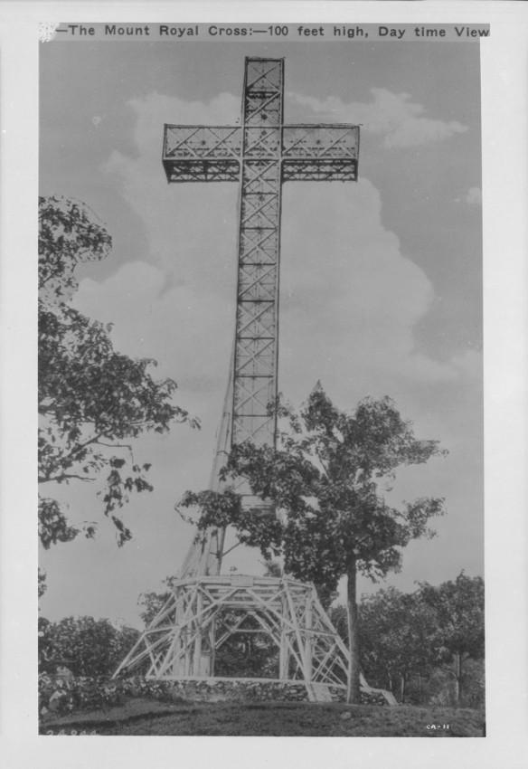 Photographie en noir et blanc d'une grosse croix en métal sur laquelle il est inscrit « The Mount Royal Cross—100 feet high, daytime view » (croix du mont Royal – 100 pieds de haut – en plein jour)