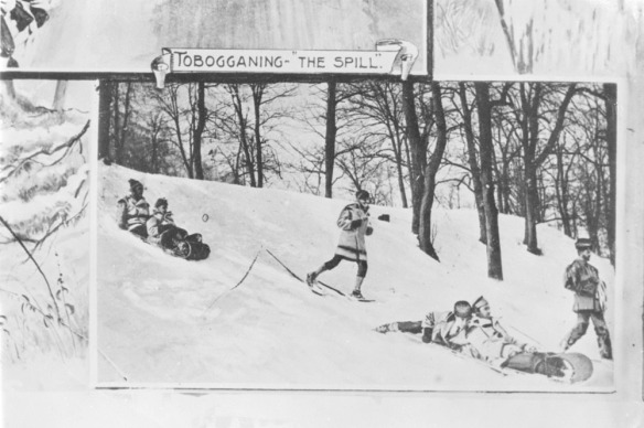 Photographie en noir et blanc d'une scène d'hiver. On y voit des personnes qui descendent une côte sur des luges ou chaussées de raquettes.