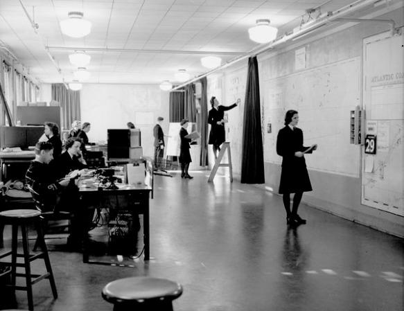 Photographie en noir et blanc de l'intérieur d'une salle des cartes bien éclairée montrant un groupe nombreux de femmes et d'hommes au travail. Dans la partie gauche de la salle, des personnes sont assises à des bureaux, tandis que dans la partie droite de la salle, des femmes vêtues d'un uniforme de couleur sombre examinent de grandes cartes fixées aux murs. L'une d'elles, montée sur un escabeau placé près du mur, reporte de l'information sur le haut d'une carte.