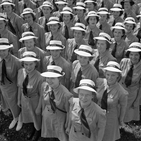 Photographie en noir et blanc d'un groupe de recrues du WRCNS souriantes, debout en rangées, les yeux levés vers l'appareil photo. Elles portent l'uniforme d'été et un couvre-chef sur lequel est inscrit « H.M.C.S. » (Her Majesty's Canadian Ship [Navire canadien de Sa Majesté]).