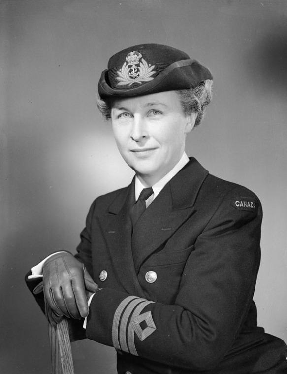 Photographie en noir et blanc d'Adelaide Sinclair, assise les bras reposant sur le dossier d'une chaise. Vêtue de son uniforme de la Marine royale (veste, blouse blanche, cravate sombre, couvre-chef et gants), elle regarde l'appareil photo et sourit légèrement.