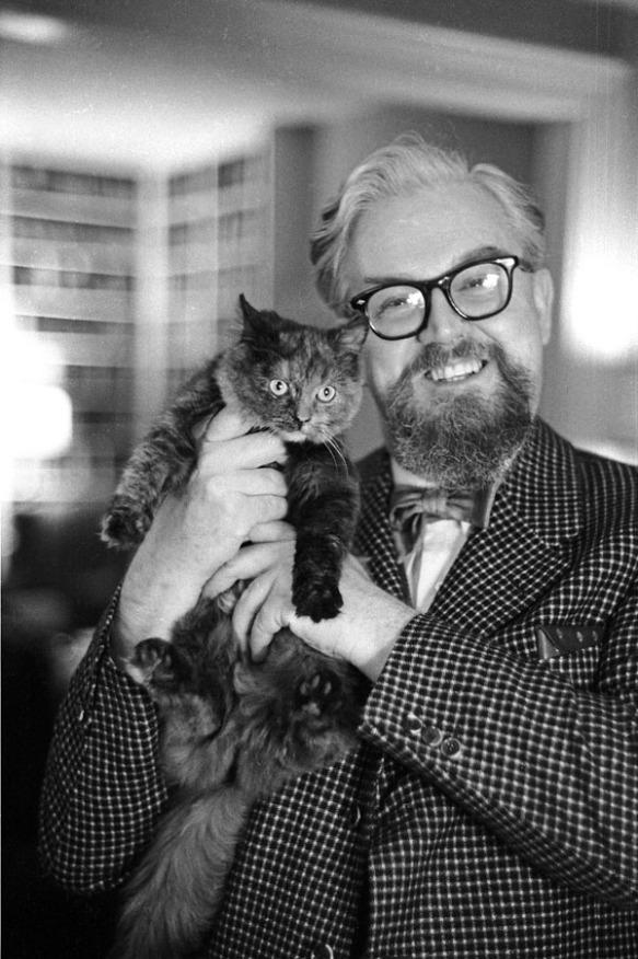 Une photo noir et blanc d'un homme souriant qui tient un chat sur son épaule.
