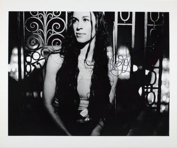 Une photo en noir et blanc d'une femme avec des cheveux long debout devant une clôture en fer forgé.