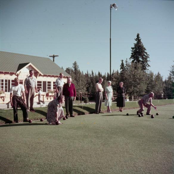 Photo couleur de deux équipes de boulingrin. Une femme et un homme sont en train de lancer leurs boules sur la pelouse.