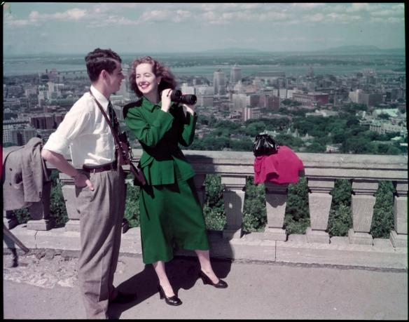 Photographie en couleurs d'un couple muni de jumelles se tenant sur le bord d'un belvédère surplombant la ville.