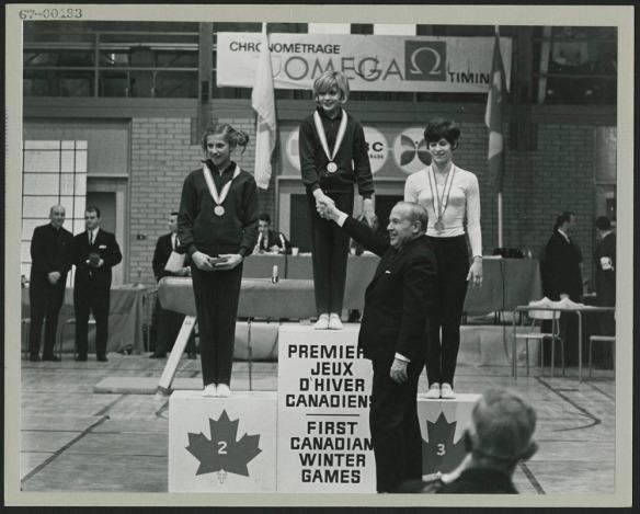Photo noir et blanc montrant un podium avec trois jeunes femmes portant des médailles. Un homme serre la main de la médaillée d'or.