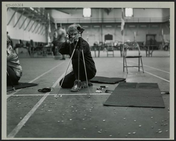 Une photo noir et blanc montrant une femme agenouillée visant avec une carabine; des cartouches vides sont parsemées sur le sol autour d'elle.