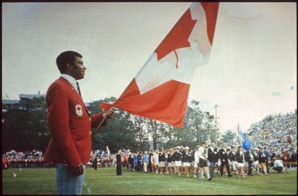 Photo en couleur d'un homme portant un veston rouge et tenant un étendard du drapeau canadien pendant que des gens paradent à l'arrière-plan.