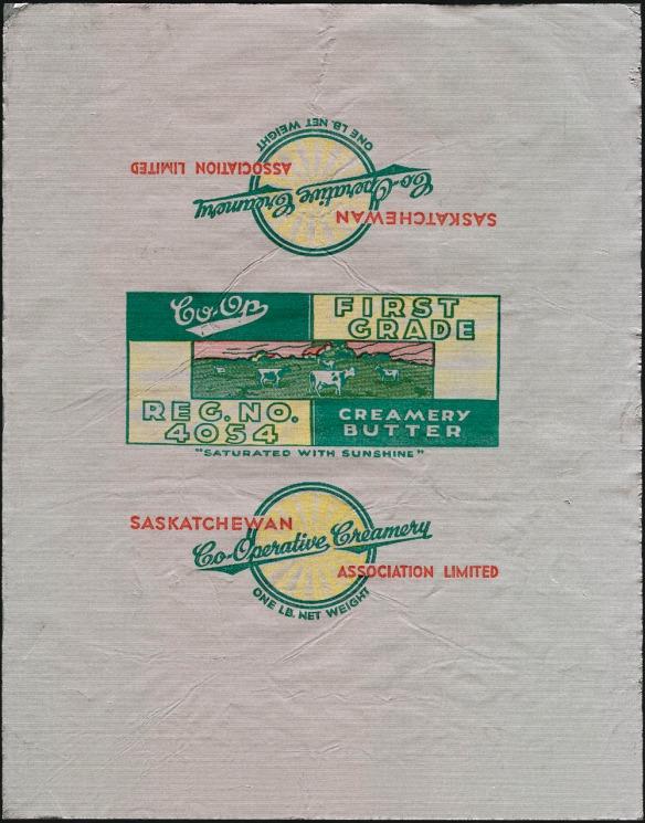 Un emballage de papier métallisé polychrome arborant une image de vaches en train de paître dans un pré. On peut y lire : « Co-op. First Grade. Creamery Butter. Reg. No. 4054 » (Co-op. Première Catégorie. Beurre de crémerie. No d'homologation 4054). Sur l'un des autres pans de l'emballage, il est écrit : « Saskatchewan Co-Operative Creamery Association Limited. One lb net weight » (Saskatchewan Co-Operative Creamery Association Limited. Poids net : une livre).