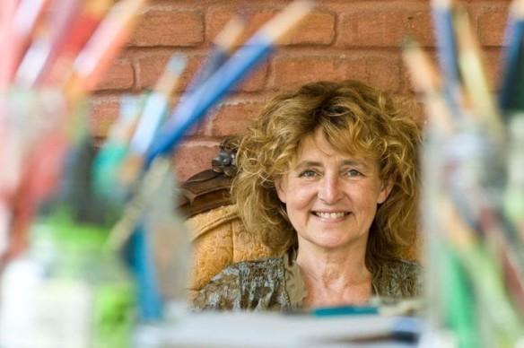 Photo en couleur d'une femme assise et souriante. On aperçoit dans l'avant plan des crayons de couleurs flou.