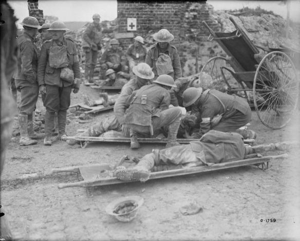 Photographie en noir et blanc de deux hommes étendus sur des brancards. Du personnel médical s'occupe d'un des deux blessés, alors que l'autre est étendu sur le côté. Plusieurs soldats se tiennent debout à gauche des brancards, et d'autres sont assis à l'arrière-plan. La scène se passe dans les décombres d'un édifice bombardé dont il ne reste qu'une cheminée.