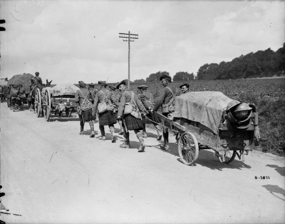 Photographie en noir et blanc d'un convoi de charrettes se déplaçant sur la route. Un groupe de soldats écossais en kilt tire la dernière charrette.