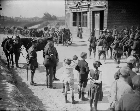 Une photographie en noir et blanc d'une colonne de soldats marchant dans une ville. Quelques officiers, des enfants et d'autres civils les regardent passer.