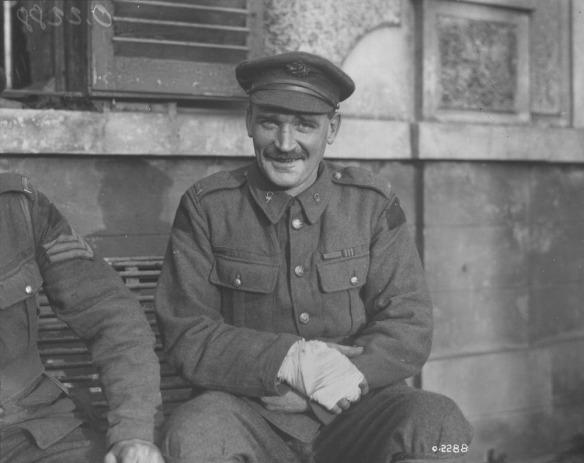 Photographie en noir et blanc d'un soldat assis, une main bandée, souriant au photographe.