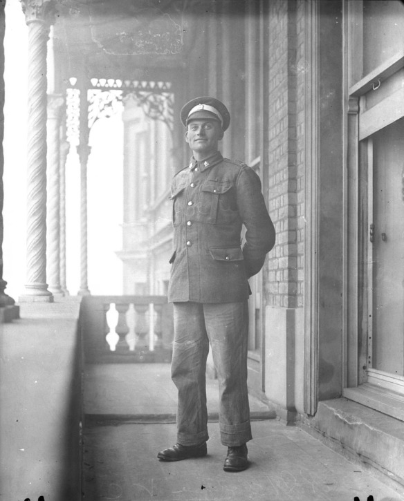 Photographie en noir et blanc d'un jeune homme en uniforme, debout sur un balcon à l'extérieur, les mains derrière le dos.