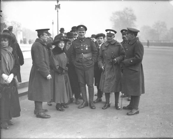 Photographie en noir et blanc d'un groupe de personnes entourant deux soldats.
