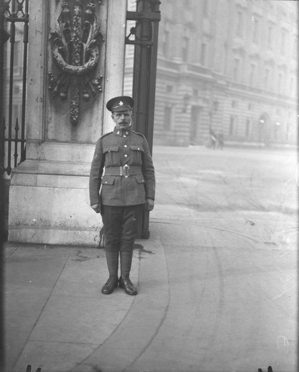 Photographie en noir et blanc d'un soldat portant un couvre-chef à visière orné d'une feuille d'érable. Il se tient au garde-à-vous devant une grande barrière menant au terrain du palais.