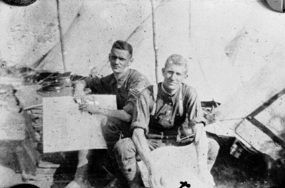 Une photographie en noir et blanc de deux jeunes hommes assis dans un camp qui consultent des cartes. Derrière eux, on voit plusieurs tentes.