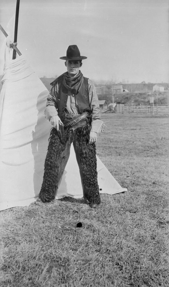 Un photo en noir et blanc d'un cowboy portant un chapeau noir, un bandana, des gants et des jambières de fourrure. Il est debout devant une tente, la main droite posée sur un pistolet dans son étui.