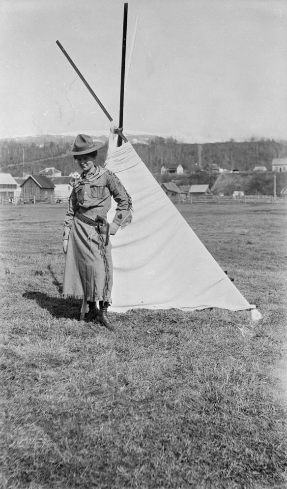 Un photo en noir et blanc d'une cowgirl portant un chapeau, un bandana, des gants ornés d'une feuille d'érable brodée et une jupe. Elle est debout devant une tente, la main gauche posée sur un pistolet dans son étui, sur sa hanche gauche.