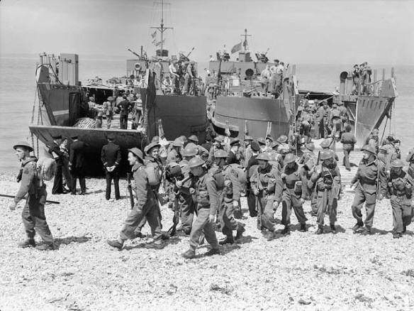 Photo noir et blanc d'un exercice de débarquement montrant des soldats quittant une péniche de débarquement et marchant sur la plage en groupes ordonnés.