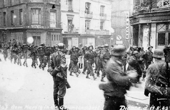 Photo noir et blanc de soldats canadiens capturés, marchant en rang dans une ville sous la surveillance de soldats allemands.