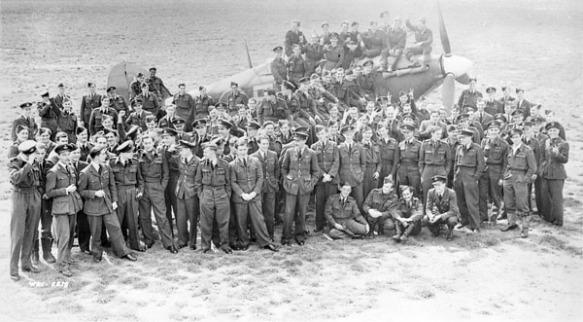 Photo noir et blanc d'un groupe d'officiers de la force aérienne posant devant un avion de chasse Hawker Hurricane.