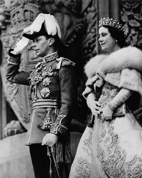 Une photographie noir et blanc du roi George VI saluant la foule à côté de la reine Élisabeth devant les édifices du parlement du Canada.
