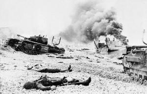 Photo noir et blanc de cadavres de soldats, d'une péniche de débarquement en feu et de chars d'assaut Churchill endommagés sur une plage de galets.