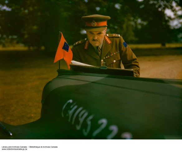 Photo couleur du major général J. H. Roberts en uniforme, examinant des documents sur le capot d'une voiture d'état-major.