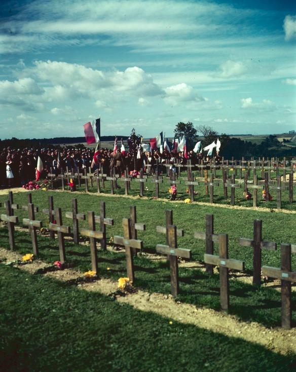 Photo couleur d'un groupe assistant à une cérémonie au cimetière militaire canadien de Dieppe, en France; à l'avant-plan, des rangées de croix temporaires marquent les sépultures.