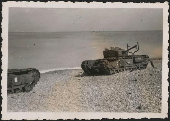 Photo noir et blanc de chars d'assaut neutralisés ou abandonnés sur la plage à Dieppe. Un des chars porte l'inscription Buttercup peinte sur le côté, parmi d'autres marques d'identification.