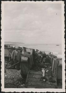 Photo noir et blanc de civils s'occupant des dépouilles de soldats morts dans une péniche de débarquement échouée sur la plage.