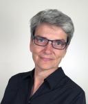 Photo en couleur d'une femme portant des lunettes regardant directement dans la caméra.