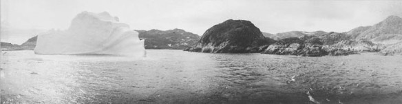 Panorama en noir et blanc d'un gros iceberg à proximité d'une île rocheuse, photographié depuis un bateau.