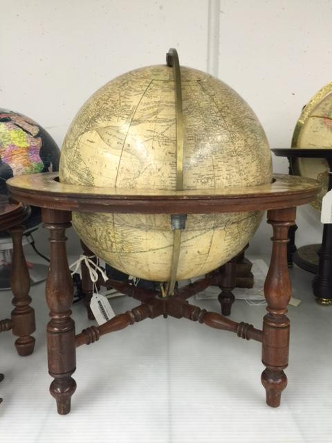 Un imposant globe terrestre dans un support en bois et en laiton.