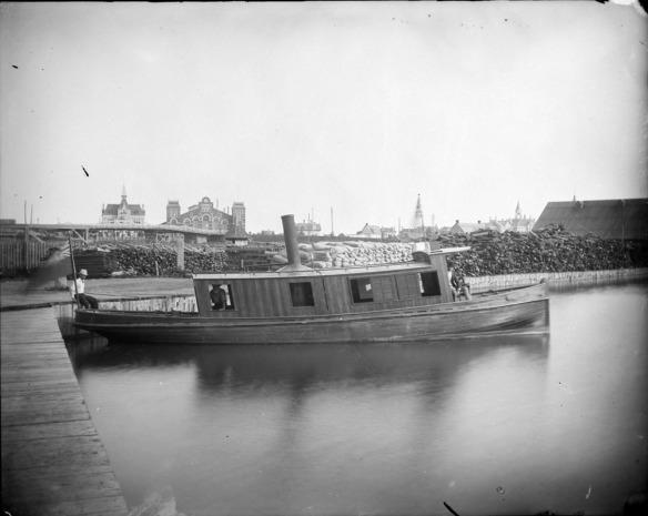 Photographie en noir et blanc d'un petit bateau à vapeur sur le canal Rideau. Trois hommes y prennent place (à la poupe, au centre et à la proue).