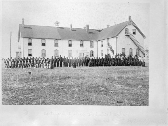Élèves en uniformes debout devant le pensionnat indien (école des métiers) de Battleford (Saskatchewan), 1895.