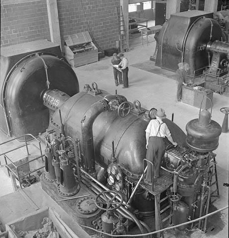 Photographie en noir et blanc d'un homme se tenant sur une petite plateforme et examinant le manomètre d'un groupe électrogène mû par turbine à vapeur.