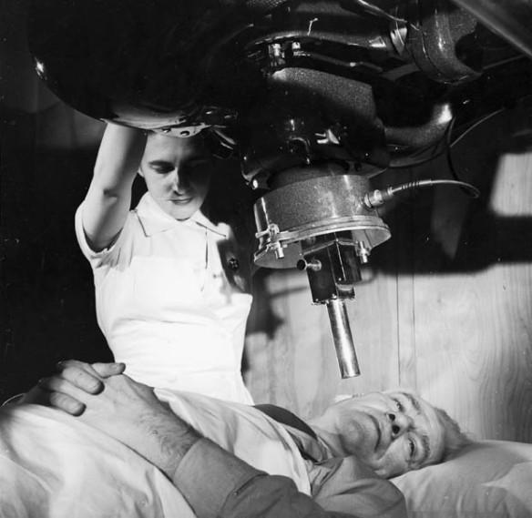 Une photographie en noir et blanc d'une infirmière qui place un appareil de radiographie sur la joue droite d'un patient. Le patient est allongé sur un lit.