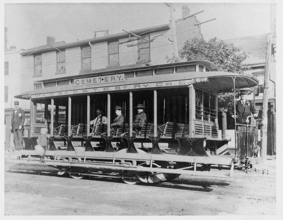 Une photographie en noir et blanc d'un tramway à ciel ouvert. Il y a un conducteur à l'avant et à l'arrière du tramway et trois passagers sont assis. Un garçon est debout sur la banquette latérale.
