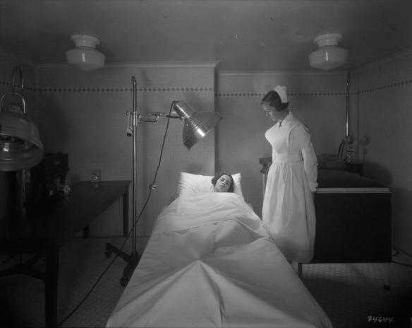 Une photographie en noir et blanc d'une infirmière prenant soin d'une patiente qui reçoit un traitement d'une lampe infrarouge. La patiente est allongée sur un lit.