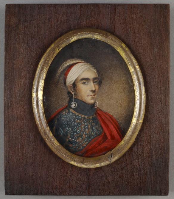 Portrait en miniature ovale du major John Norton, Teyoninhokarawen, portant une coiffe rouge et blanche dans laquelle est piquée une plume d'autruche. Il porte aussi de longues boucles d'oreilles composées d'étoiles encerclées, une chemise à motifs et une cape rouge.