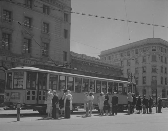 Une photographie en noir et blanc montrant des hommes et des femmes faisant la queue à un point de ramassage pour monter à bord d'un tramway encloisonné.